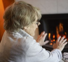 old lady warming hands near fire